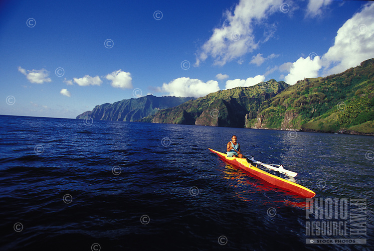 Local man paddling an outrigger canoe off the coast of Fatu Hiva, Marquesas, French Polynesia
