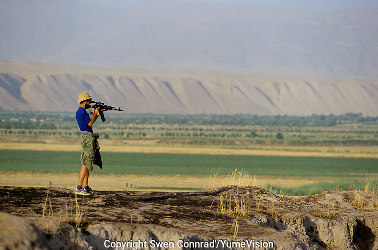 A Russian border guard on the Tadzhik-Afghan frontier at P'andz, with electric barbed wire, anti personal mine, mirador and Russian military patrol.
