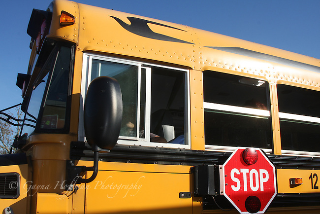 Side view of school bus with stop sign attached.