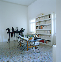 The multicoloured terrazzo floor makes an interesting contrast with the flat matt walls in the dining room