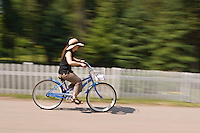 A woman in a sun hat bicycles around Mackinac Island in Michigan.