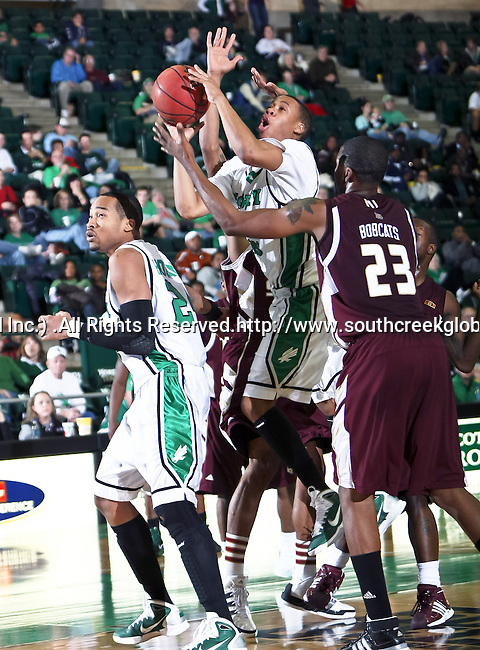 North Texas Mean Green guard Tristan Thompson (14) drives in for a lay up past Texas State Bobcats forward Cameron Johnson (23) in the game between the Texas State Bobcats and the University of North Texas Mean Green at the North Texas Coliseum,the Super Pit, in Denton, Texas. UNT defeated Texas State 85 to 62