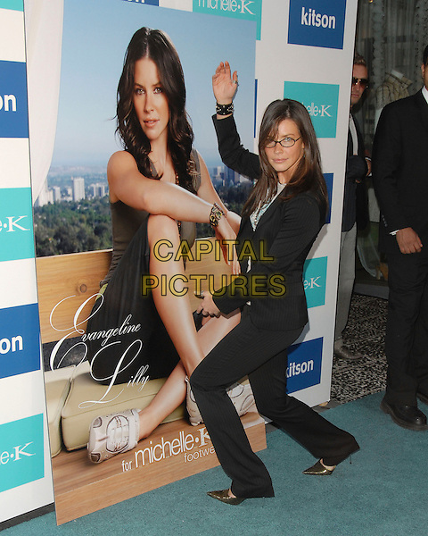 EVANGELINE LILLY.photocall for The New Face of MICHELLE K. Modern , Chic Footwear at Kitson Boutique in Beverly Hills, California, USA, June 15, 2006..full length straight hair glasses funny pose arms poster.Ref: DVS.www.capitalpictures.com.sales@capitalpictures.com.©Debbie VanStory/Capital Pictures