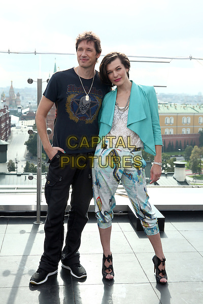 Paul W. S. Anderson & Milla Jovovich.Photocall for 'Resident Evil: Retribution', Moscow, Russia..September 6th, 2012.full length blue turquoise blazer white lace top cropped print trousers black sandals shoes black t-shirt jeans denim married husband wife.CAP/PER/PK.©AM/PersonaStars/CapitalPictures