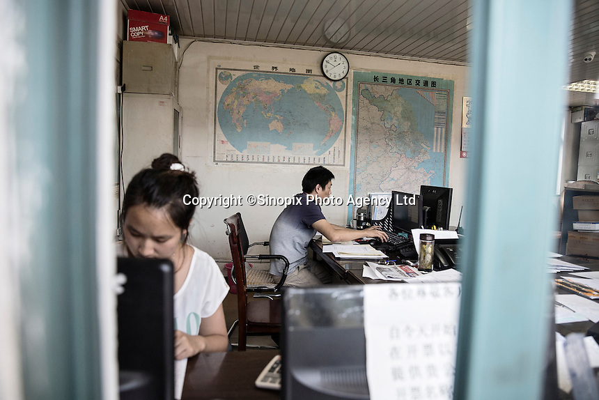 Office workers at a small logistics company in Xingxing village on the outskirts of Shanghai,  China on 14 August 2015.  As China's sputtering economy has beginning to affect employment, many migrants who used to live in the village to work on Shanghai's numerous construction sites and factories are beginning to thin out.