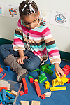 Education preschool 3 year olds girl sitting in block area, building with colored blocks creating small constructions by color