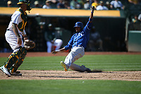 OAKLAND, CA - AUGUST 16:  Alcides Escobar #12 of the Kansas City Royals slides home safely against the Oakland Athletics during the game at the Oakland Coliseum on Wednesday, August 16, 2017 in Oakland, California. (Photo by Brad Mangin)