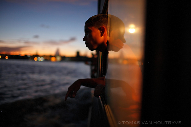 A boy looks out the window of a ferry boat crossing the bay of Havana, in Cuba on 11 October 2008.