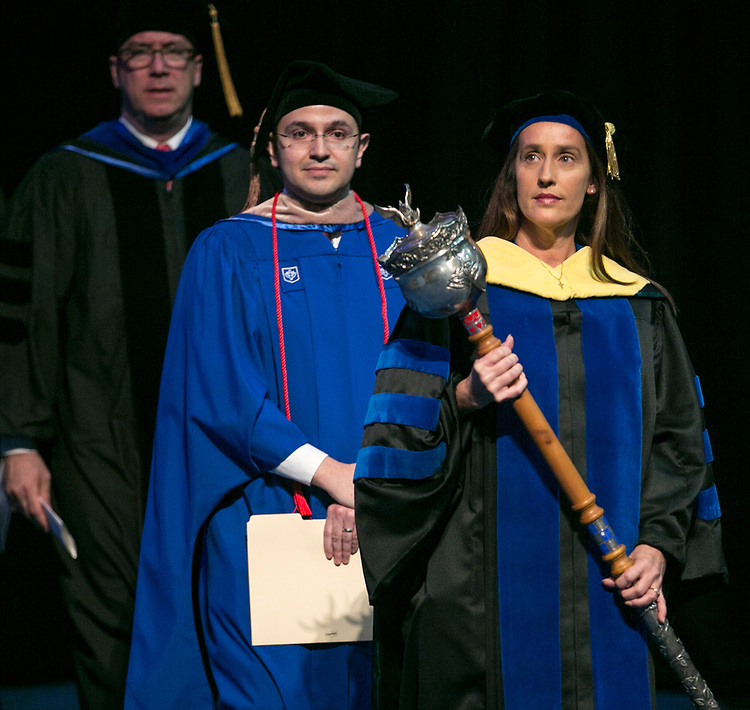 Misty M. Johanson, associate dean, carries the university mace and serves as the university marshal Sunday, June 11, 2017, during the DePaul University Driehaus College of Business commencement ceremony at the Allstate Arena in Rosemont, IL. (DePaul University/Jamie Moncrief)