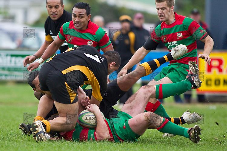 Grant Henson crashes to ground in the tackle of Toni Pulu and Peter Mata. Counties Manukau Premier Club Rugby game between Waiuku and Bombay, played at Waiuku on Saturday July 5th 2010. Waiuku won 59 - 14 after trailing 12 - 14 at halftme.