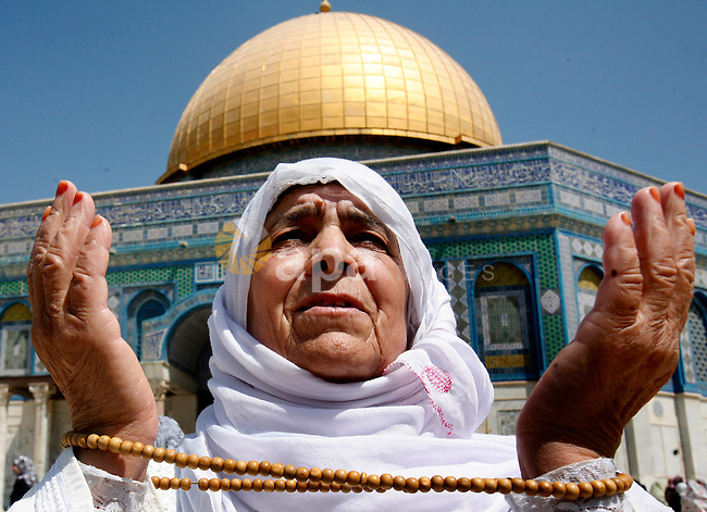A Palestinian female worshiper prays outside the Dome of the Rock at the al-Aqsa mosque compound in Jerusalem during the third Friday prayers of the Muslim holy month of Ramadan on 03 August 2012. Muslims fasting in the month of Ramadan must abstain from food, drink and sex from dawn until sunset. Photo by Mahfouz Abu Turk