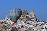 A  hot air balloon navigates  below the ancient town of Uchisar in the Cappadocian region of Central Turkey.