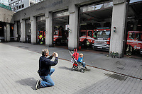 (Oslo July 26, 2011)  A man takes a picture of a boy outside the main fire station, which was also quite damaged by the terror bombing...A large vehicle bomb was detonated near the offices of Norwegian Prime Minister Jens Stoltenberg on 22 July 2011. .Another terrorist attack took place shortly afterwards, where a man killed 68 people, mainly children and youths attending a political camp at Utøya island. ..Anders Behring Breivik was arrested on the island and has admitted to carrying out both attacks..(photo:Fredrik Naumann/Felix Features)