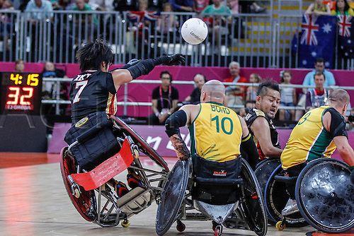 08.09.2012 London, England.  Daisuke IZEZAKI (JPN) offloads as he his floored by Chris BOND (AUS) during  their teams' semi-final in the wheelchair rugby competition from The Basketball Arena in the Olympic Park, Stratford, London on Day 10 of the 2012 Paralympic Games.  Final score: Great Britain 38-49 Japan.  Japan advance to the semi-finals.