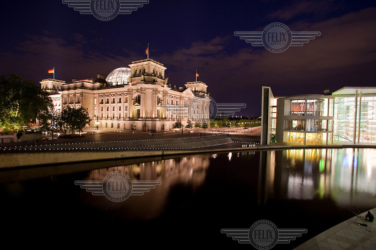 A night fisherman on the banks of the Spree River with a view of the Reichstag, the restored German Parliament which once again became the seat of the German government in 1991 after the reunification of East and West Germany. The building on the right is the Paul Lobe Haus, another parliamentary building.