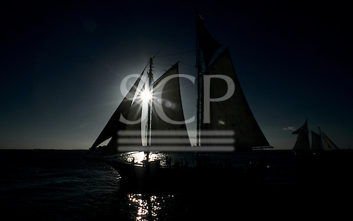 Florida, USA. Sailing ship silhouetted against silver sunlight reflected of sea in Key West.