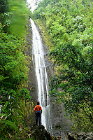A young boy (age 9) enjoys the tranquil scenery of Manoa Falls located in Manoa Valley, Oahu.