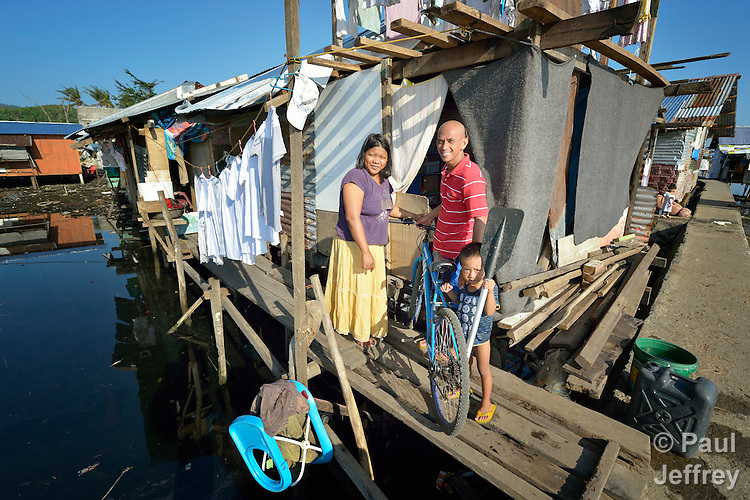 "Rachel and Rennel de la Cruz, and their son John Ray, have rebuilt a temporary shelter where their home once stood in Tacloban, a city in the Philippines province of Leyte that was hit hard by Typhoon Haiyan in November 2013. The storm was known locally as Yolanda. The dwelling is in a ""no build"" zone declared by the Philippine government, and the family says they're hoping the government will make it possible for them to build a permanent house elsewhere."