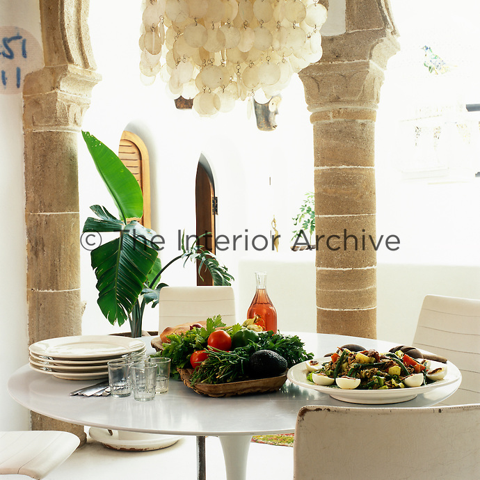 A platter of fresh vegetables and a salad Nicoise laid out on a Saarinen tulip table for lunch