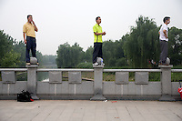 Spectators stand on a bridge railing as they watch the Nanjing, China, leg of the 2008 Olympic Torch Relay.