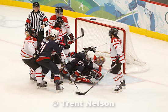 Trent Nelson  |  The Salt Lake Tribune.USA's Jenny Potter drives into Canada goalkeeper Shannon Szabados. USA vs. Canada, gold medal game, women's Ice Hockey at the Canada Hockey Place, Vancouver, XXI Olympic Winter Games, Thursday, February 25, 2010.