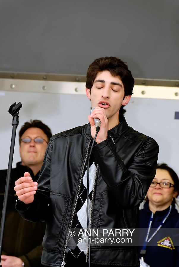 APRIL 16, 2011 - MERRICK, NY: Robbie Rosen, American Idol Season 10 Top 16 contestant, on stage singing with eyes closed, being honored at Robbie Rosen Day at Merrick Kidfest presented by Merrick Chamber of Commerce, with, in background, its members and some area politicians also on stage, at his hometown of Merrick, Long Island, New York, USA. (EDITORIAL USE ONLY)