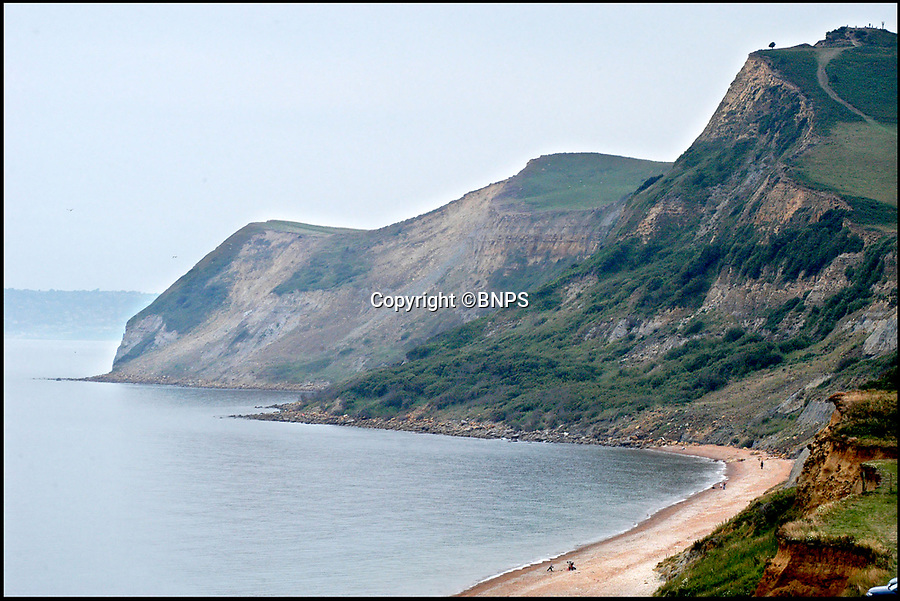 BNPS.co.uk (01202 558833)Pic:  BNPS<br /> <br /> Cliffs near Charmouth, Dorset.<br /> <br /> This is the heart-stopping moment two walkers were saved from drowning after being cut off by the tide.<br /> <br /> Dramatic video footage from a coastguard helicopter shows the strong waves of the incoming tide licking at the feet of the young couple.<br /> <br /> They were rescued in the nick of time by a coastguard winchman who plucked them off the beach at Charmouth, Dorset.