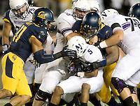 California defenders tackle Venric Mark of Northwestern during the game at Memorial Stadium in Berkeley, California on August 31st, 2013.  Northwestern defeated CAL, 44-30.