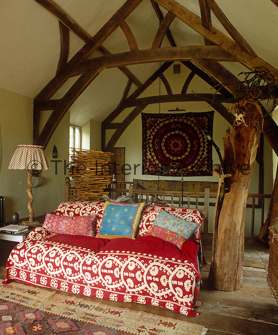 The living room sofa is covered with an antique red and white fabric