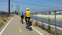 Holland, on his Yedoo kick scooter, and Michelle, on her Terry Burlington city bike, ride the Los Angeles River Greenway Trail during the 2017 (17th annual) Los Angeles River Ride.  The river is mostly water in this area, and the 5 freeway is visible to their left.