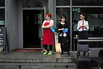 Three waitresses watching crowds marching through the streets of Berlin during a demonstration by the Alternative für Deutschland (AfD) political party. Around 5000 supporters of the AfD took part in the march and rally calling on German Chancellor Angela Merkel to halt the influx of refugees into the country. Around one million refugees from the Middle East and north Africa arrived in Germany during 2015, 50,000 of whom came to Berlin.