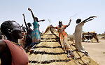 Women displaced by violence in Sudan's Darfur region put the finishing touches on a thatched roof, celebrating with song and dance as they go, in the Abu Jabra IDP Camp.
