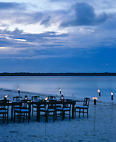 As night falls a table is laid out on the shore illuminated by torcheres and hurricane lamps, setting the scene for dinner under the stars