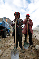 China started building a controversial 67-mile &quot;paved highway fenced with undulating guardrails&quot; to Mount Qomolangma, known in the west as Mount Everest, to help facilitate next year's Olympic Games torch relay./// Two young women work with a shovels building the road to Everest Base Camp.<br /> Tibet, China<br /> July, 2007