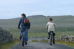 cycliste sur les petites routes de l'île d'Inishmore. Au fond le  fort Dun Aengus.cyclist on the small road of Inishmore island