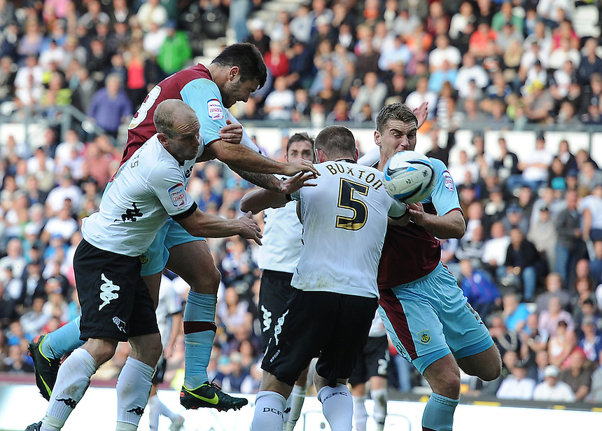 Burnley's Charlie Austin beats Derby County's Gareth Roberts and Jake Buxton to the ball and scores his and his sides second goal in the last minutes of the match to secure a 2-1 victory ..Football - npower Football League Championship - Derby County v Burnley - Saturday 22nd September 2012 - Pride Park - Derby..