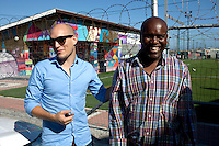 Khayelitsha, South Africa March 5, 2013: Amandla EduFootball founder Florian Zech with the nearby school principal Lulama Maji outside the field in Khayelitsha a poor township outside Cape Town, South Africa. They use football to initiate, support educational projects for youth in the township. The program keep children busy and it decreases the risk of them joining gang, criminal activity or teenage pregnancy. The crime level has decreased substantially in the area since the program was created in 2006. (Photo by: Per-Anders Pettersson)