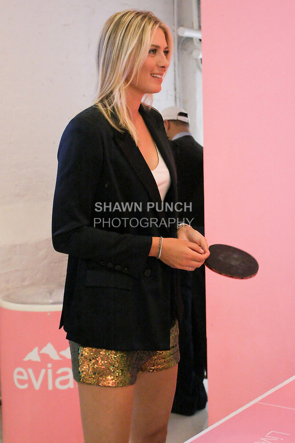 """Maria Sharapova plays table tennis with AJ Calloway from Extra TV during the Evian """"Live Young"""" photo shoot event hosted by Maria Sharapova at Openhouse Gallery on August 24, 2010."""