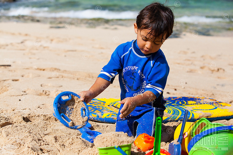 A young local Hawaiian boy plays with toys on a sandy beach on O'ahu.