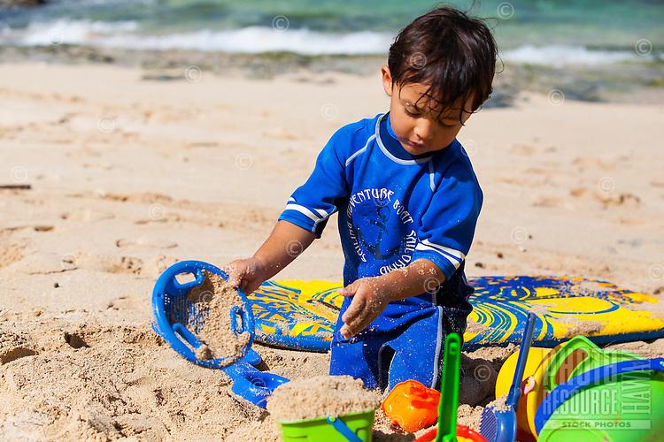 A young local Hawaiian boy plays with toys on a sandy beach on O'ahu.