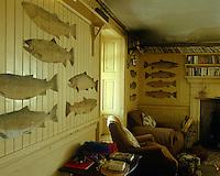 The clapboard walls of the comfortable living room at the fishing lodge are decorated with paper cutouts of salmon