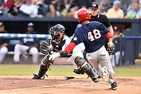 Asheville Tourists catcher Chris Rabago (22) fields the ball and tags out Blake Perkins (48) as home plate umpire Sam Burch waits to make the call during a game against the Hagerstown Suns at McCormick Field on September 4, 2016 in Asheville, North Carolina. The Suns defeated the Tourists 10-5. (Tony Farlow/Four Seam Images)