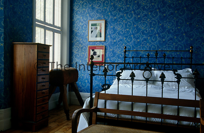 A gym horse stands beneath the window in this bedroom with walls that feature a blue and yellow patterned wallpaper