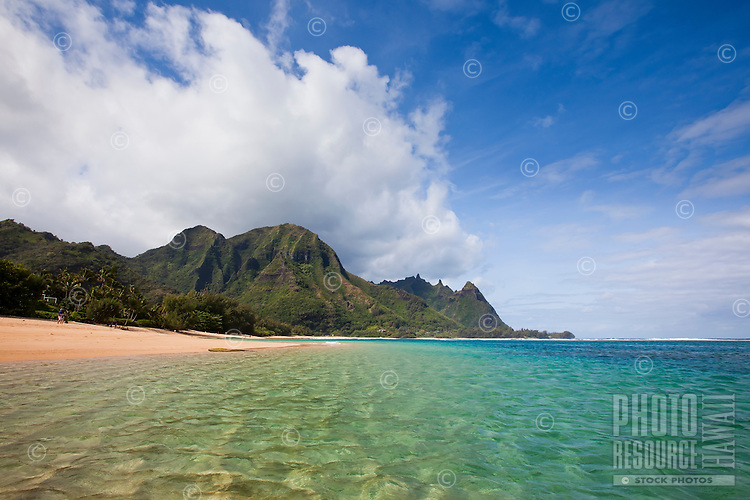 Makua Beach coastline with clear blue water and white sand beach with Mount Makana in the background
