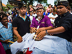 13 JULY 2016 - UBUD, BALI, INDONESIA:  The burned bones of a member of the community are wrapped after his cremation. Local people in Ubud exhumed the remains of family members and burned their remains in a mass cremation ceremony Wednesday. Almost 100 people will be cremated and laid to rest in the largest mass cremation in Bali in years. Most of the people on Bali are Hindus. Traditional cremations in Bali are very expensive, so communities usually hold one mass cremation approximately every five years. The cremation in Ubud will conclude Saturday, with a large community ceremony.     PHOTO BY JACK KURTZ