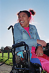 Young woman with Cerebral Palsy sitting in wheelchair outdoors in park laughing.  MR