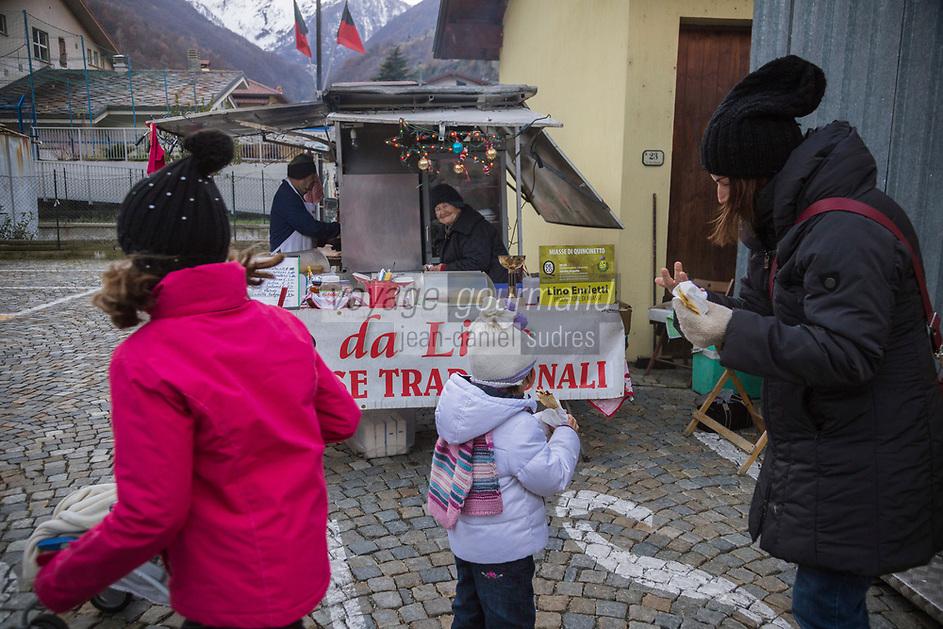 Italie, Val d'Aoste, Bard: Sur le marché de Noël: Dégustation des Miasse , La miassa est une  crêpe locale à base de farine de maïs / Italy, Aosta Valley, Bard:  Christmas market: Eating  Miasse, The Miassa is a local pancake made of cornmeal