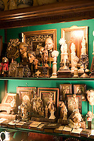 A collection of antique items, including prayer books, religious artefacts and figurines are displayed in a glass cabinet