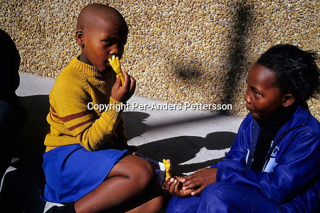 education,food,lunch,poverty,.Girls eat fried chicken feet during a lunch break on June 17, 2004 in Yomelela primary school in Khayelitsha, the biggest black township, about 20 miles outside Cape Town, South Africa. Some of the students  dance in a ballet school called Dance For All, which teaches about 200 unprivileged children dance after school. Many children are talented and the discipline taught during the dance classes has helped many to improve their concentration in school. The township is struggling with poverty, high unemployment and a growing problem with HIV-Aids. .©Per-Anders Pettersson/iAfrika Photos.......