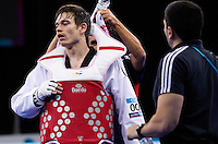 04 DEC 2011 - LONDON, GBR - Aaron Cook (GBR) recovers after beating Yousef Karami (IRI) during their men's -80kg category quarter final round contest at the London International Taekwondo Invitational and 2012 Olympic Games test event at the ExCel Exhibition Centre in London, Great Britain (PHOTO (C) NIGEL FARROW)